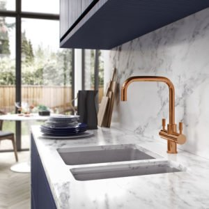 A sleek brass tap is mounted over a sink set into a white marble counter top. There are blue kitchen cabinets and blue plates in the background, behind which you can see a modern kitchen table and French doors with a view of the garden beyond.