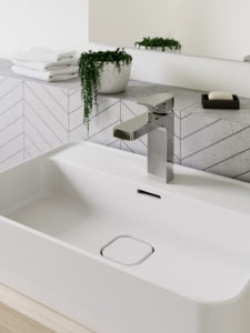 A sleek, modern white sink with square chrome tap, in front of a classy tiled wall. On a ledge above is a small trailing plant, folded white flannels and a mirror reflecting the cream walls.