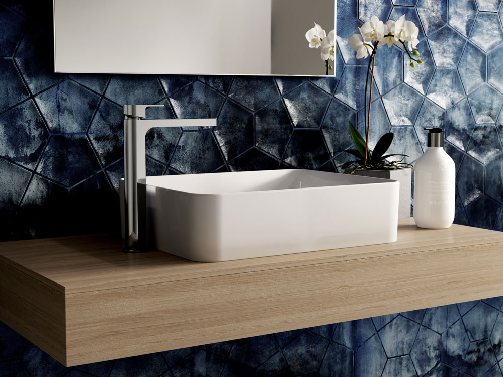 Eye-catching blue pentagonal tiles cover a bathroom wall, on which is a floating wooden shelf. There is a white ceramic sink with a modern chrome tap, with a white potted orchid and white bottle of shampoo next to it, above which sits a simple rectangular mirror.