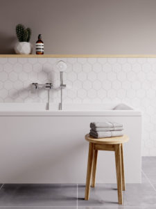 A clean, modern bath side with hexagonal tiles behind it and a silver showerhead. There are towels neatly folded on the stool to the front, and a small cactus on the wall.